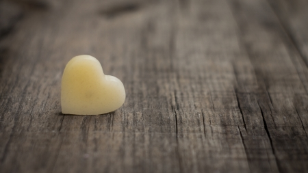 romatic: A beige heart out of wax on wooden background
