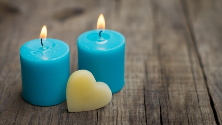 Blue burning candles with a heart on wood background. Stock Photo