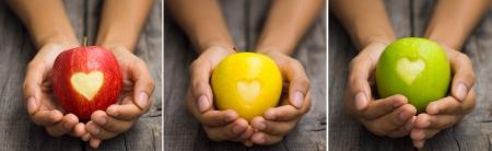 木製の背景に刻まれた心と 3 つの異なるリンゴを保持している人
