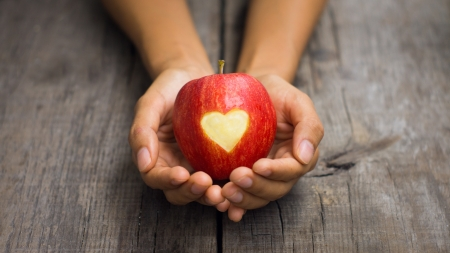 Een persoon die een rode appel met gegraveerd hart