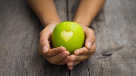 Een persoon die een groene appel met gegraveerd hart Stockfoto