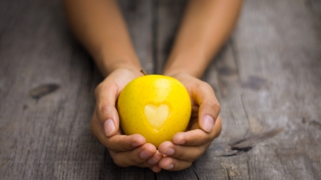 A person holding a Yellow Apple with engraved heart Stock Photo - 21818338