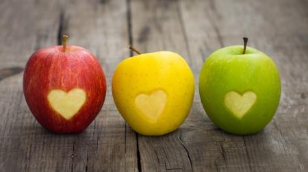 Drie appels met gegraveerde hartjes op houten achtergrond