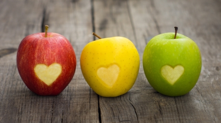 Three apples with  engraved hearts on wood background Archivio Fotografico
