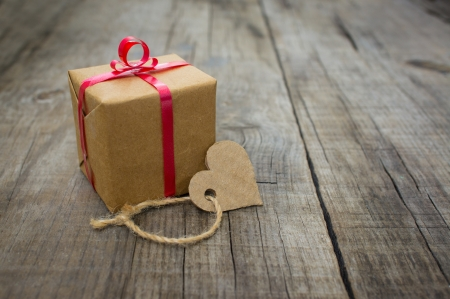A small Gift with a paper heart on wood background