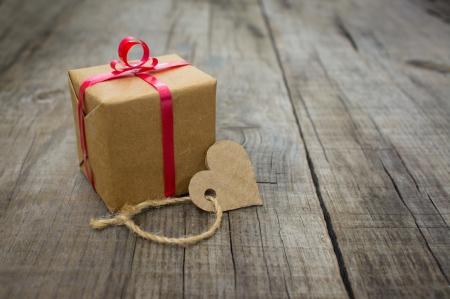 Ein kleines Geschenk mit einem Herz aus Papier auf Holz Hintergrund Standard-Bild - 21818341