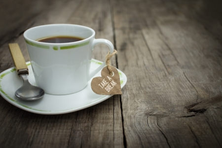 A coffee cup with a paper heart on wooden background.  photo