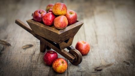 achievment: Red Apples in a miniature wheelbarrow on wood background