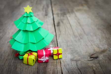 minature: Paper miniature christmas tree with present on wood background Stock Photo