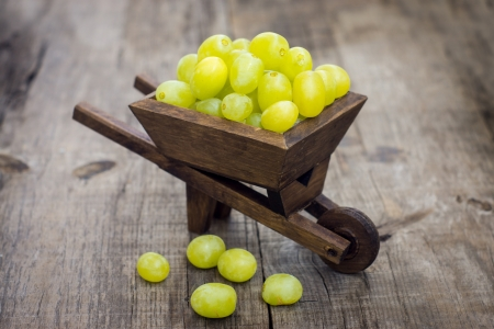 A wheelbarrow full of fresh green grapes on wood background Stock Photo - 21960825