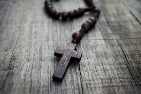 A  rosary with beads on wooden textured background.  Archivio Fotografico