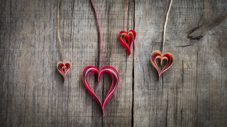 Hanging paper heart decoration on wood background.  Standard-Bild