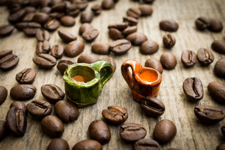 Miniature coffee cups with coffee beans on wood background Stock Photo - 22025611