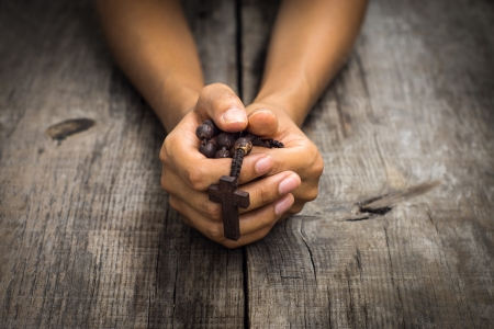 A person praying holding a rosary in the hands on wood background.