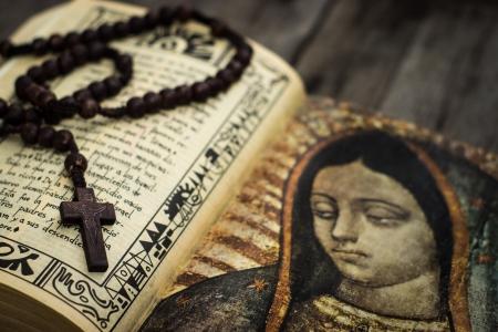Een religieuze concept van een rozenkrans en een bijbel op hout achtergrond Stockfoto