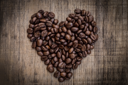 A heart shaped out of coffee beans on wood background
