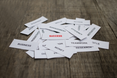 Paper strips with Success related words on wooden background