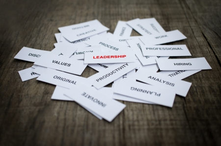 Paper strips with Leadership related words on wooden background Фото со стока