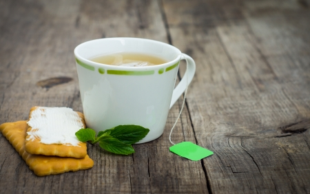 cup: A cup of mint tea with cookies on wood background