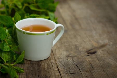 A cup of mint tea on wood textured background