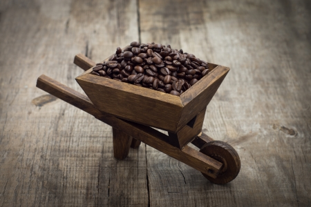A wheelbarrow full of coffee beans on wood background