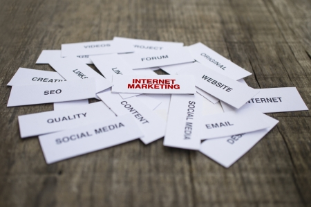Paper strips with Internet Marketing related words on wooden background Фото со стока