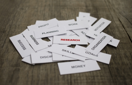 Paper strips with Research related words on wooden background