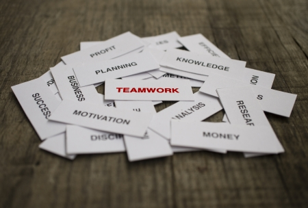 Paper strips with Teamwork related words on wooden background