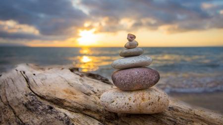 Zen Stones auf einem Baumstamm und Sonnenuntergang im Hintergrund.