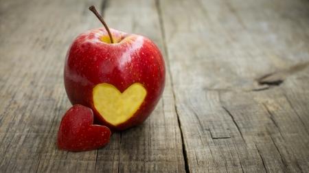 Een rode appel met gegraveerd hart op hout achtergrond Stockfoto
