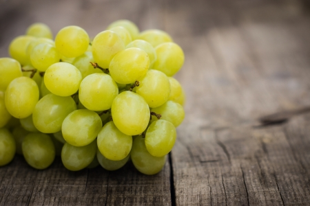 Fresh Green grapes on wood textured background.
