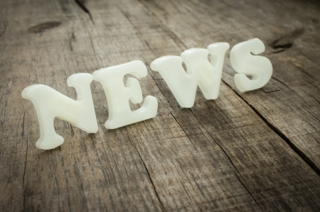 News out of plastic letters on wood background photo