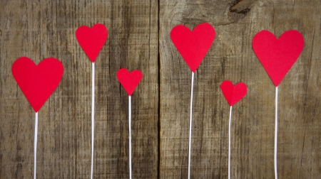 Several Red Hearts on wooden textured background.