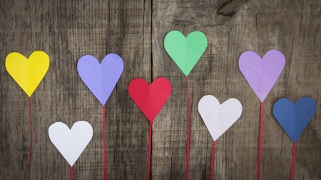 romatic: Several colorful paper hearts on wooden textured background Stock Photo