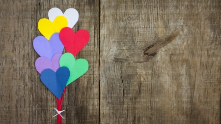 Several colorful paper hearts on wooden textured background photo