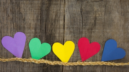 Colorful paper hearts on wood textured background