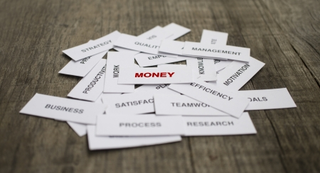 Paper strips with Money related words on wooden
