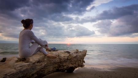 Donna seduta su un tronco d'albero, godersi il tramonto