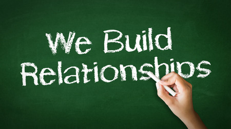 A person drawing and pointing at a We Build Relationships Chalk Illustration Фото со стока - 25604201