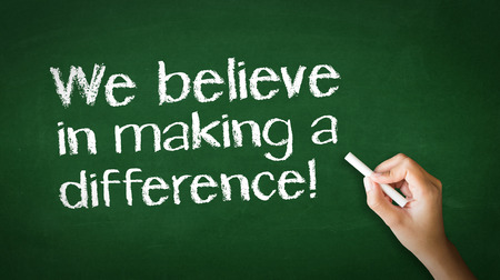 A person drawing and pointing at a We believe in making a difference Chalk Illustration Stockfoto