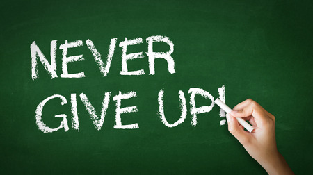 A person drawing and pointing at a Never Give Up Chalk Illustration