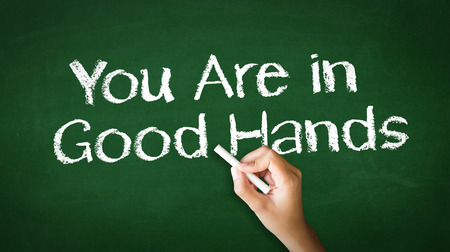 A person drawing and pointing at a Your Are in Good Hands Chalk Illustration