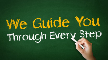 A person drawing and pointing at a We guide you through every step Chalk Illustration Stockfoto
