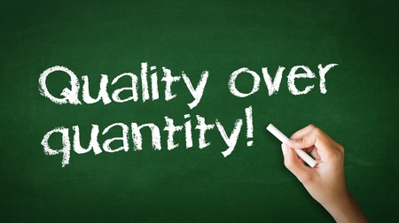 quantity: A person drawing and pointing at a Quality over Quantity Chalk Illustration