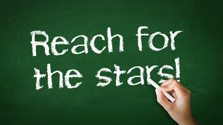 A person drawing and pointing at a Reach for the stars Chalk Illustration Stockfoto