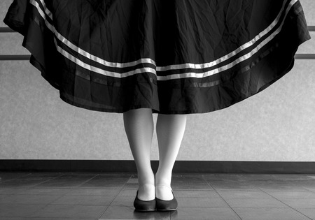 Black and white version of Traditional dancer holding her character skirt out with her feet in parallel position in the dance class