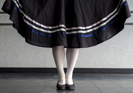 Traditional dancer holding her character skirt out with her feet in parallel position in the dance class