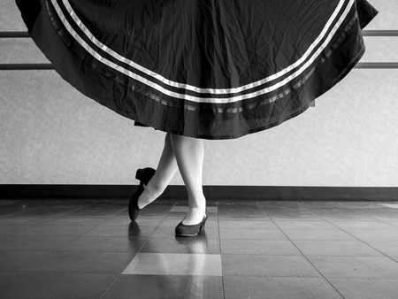 Black and white version of Dancer in Classical position with skirt held in character ballet attire Imagens