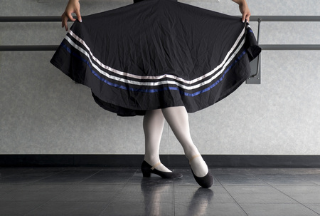 Teenager doing character ballet dance with skirt held in preparation