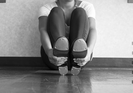 Black and white version of Female dancer sitting in tap class holding tap shoes 版權商用圖片